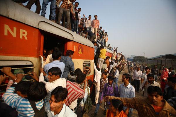 Commuters struggle to enter a train at Noli Railway Station in Uttar Pradesh